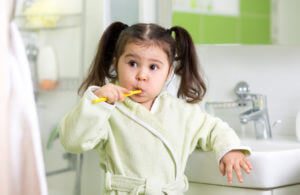 Child little girl brushing teeth in bath