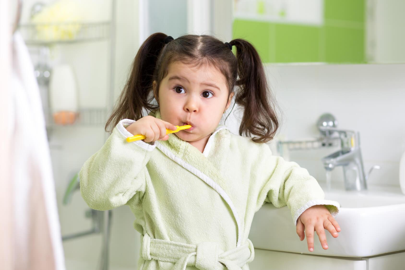 Child little girl brushing teeth in bath