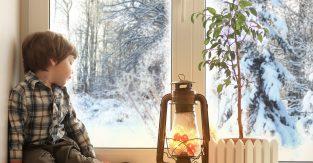 Niño sentado al lado de una ventana