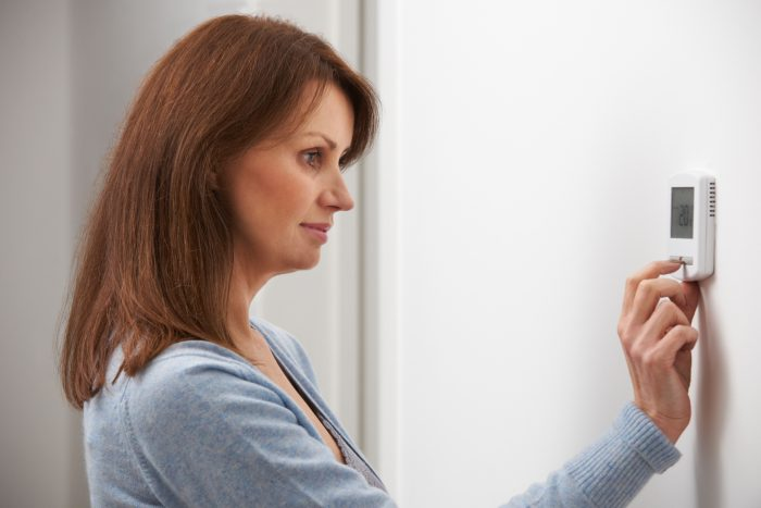 Mujer regulando termostato