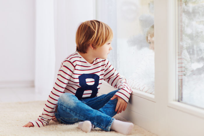 Niño sentado mirando por la ventana