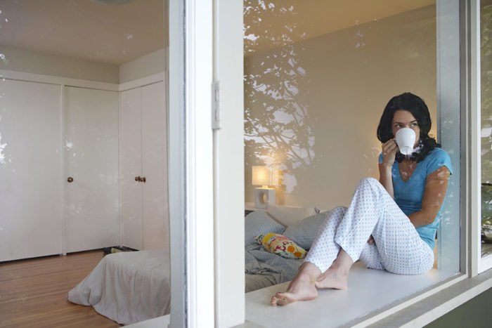 Mujer sentada al lado de la ventana