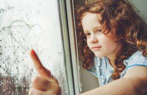 Niña dibujando un corazón en la ventana
