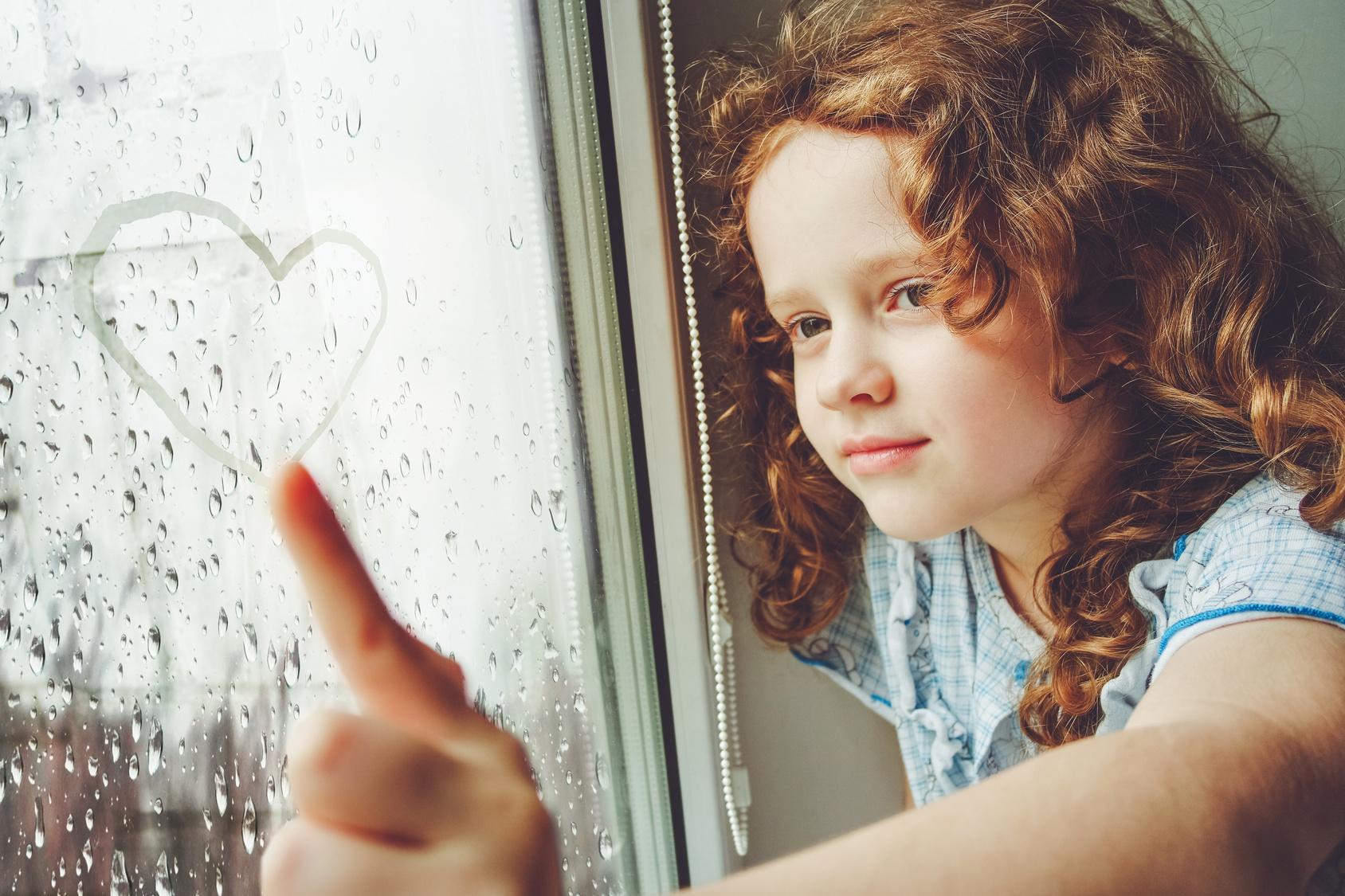 Niña feliz dibujando un corazón en la ventana
