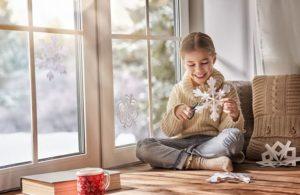 niña jugando al lado de unas ventanas de pvc